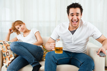 young boy watching football in the television with a beauty girl