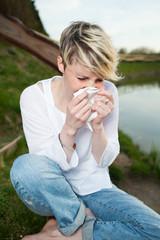 junge frau niest in taschentuch