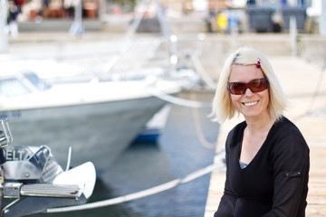 Blonde woman smiling in yacht harbour