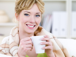 Smiling woman warming with cup