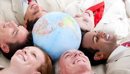 Multi-ethnic business people lying around a globe