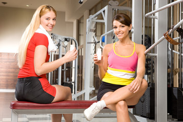 Two girlfriends relaxing in a gym