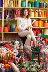 Woman Sitting On Stool Holding Knitting Needles In Front Of Yarn