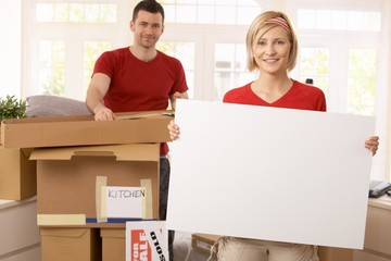 Smiling couple unpacking in new place