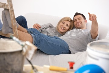 Smiling couple relaxing after painting