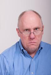 Older Balding Man in Blue Shirt Looking Mad