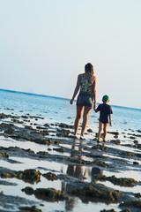 Mum and the son walk on a coast