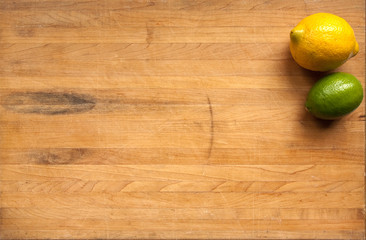 Lemon and lime on a worn butcher block cutting board