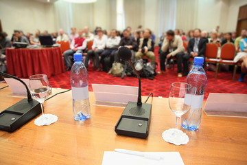 conference in hall. bottle, microphone, glass and pen on table