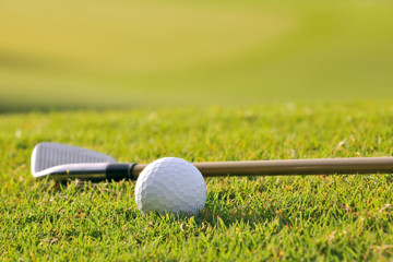 golf ball and club on fairway backlit