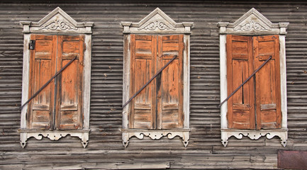 Three old faded wooden windows with closed shutters