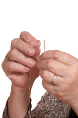 Hands of the old woman pass  thread in  needle