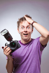 Portrait of excited surprised photographer with camera at hand