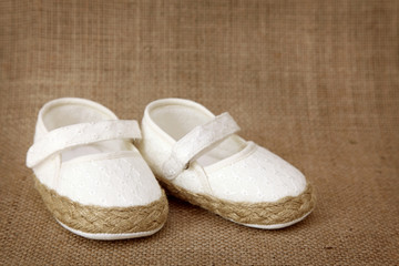 White baby shoes on brown background