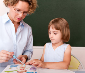 Little girl working under the supervision of a teacher