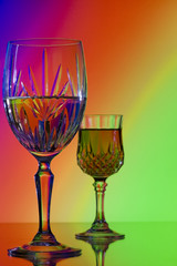 Two wine glasses on bright colorful rainbow background