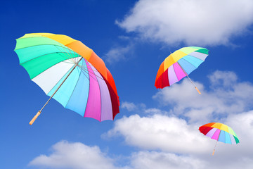 Three rainbow umbrellas flying in a rich blue sky.