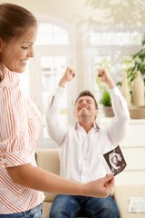 Smiling parents with ultrasound baby image