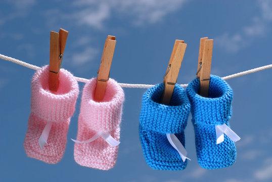 chaussons de bébé rose et bleu sur un fil de linge