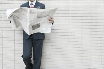 屋外で新聞を読むビジネスマン