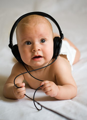 white baby in black headphones