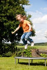 Kind auf Trampolin im Garten