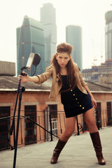 The girl-musician on a roof with a microphone