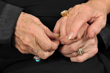Two senior adult women holding each others hands
