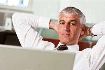 Geschaeftsmann arbeitet am Laptop und lehnt sich zurück