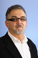 Serious mature businessman with glasses against blue