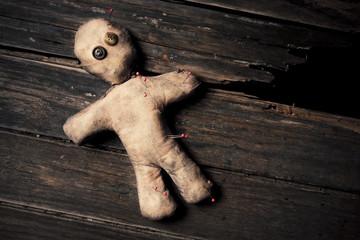 creepy voodoo doll on wooden floor