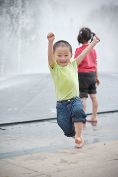 happy asian boy and girl play by Fountain
