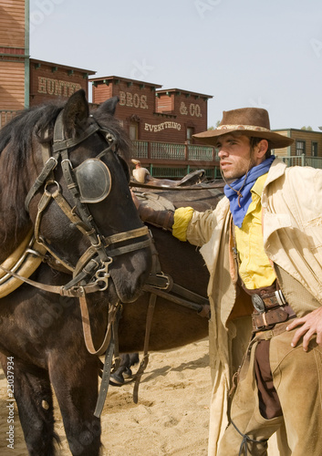 Wall mural Cowboy standing next to his horse