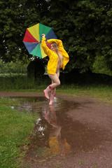 Frau tanzt im Regen mit Schirm und Regenjacke