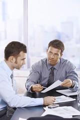Businessmen discussing report