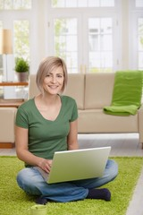 Happy woman with laptop at home