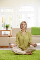 Woman doing yoga meditation at home
