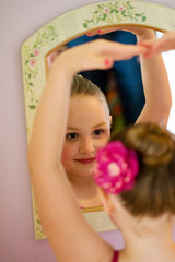 child ballerina looking in mirror