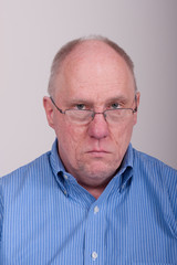 Older Balding Man in Blue Shirt Looking Unhappy Over Glasses