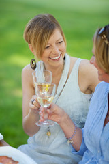 lachenende frauen trinken weißwein