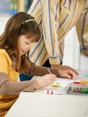 Schoolgirl painting in art class at elementary school