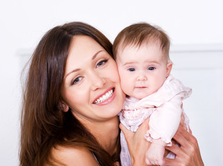 Portrat of happy mother with baby at home