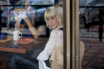 Girls in cafe. The photo through glass