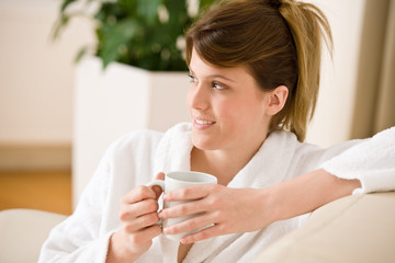 Young woman in white bathrobe with coffee