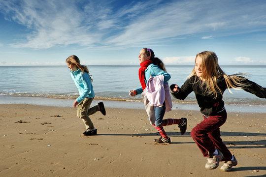 Trois enfants font la course sur la plage