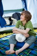 junge mit fußball sitzt vor dem zelt
