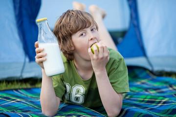 junge isst apfel vor dem zelt