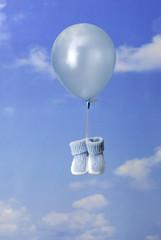 concept de naissance: chaussons bleu attaché à un ballon
