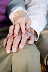 Hands of elderly couple touching on knee