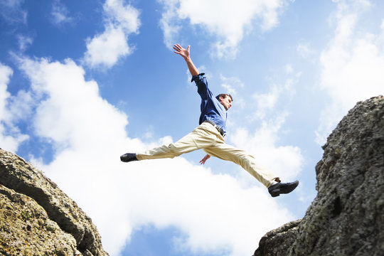 Businessman jumping over the mountains, business concept